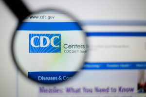 A photo of the CDC's website. There is a magnifying glass over the CDC logo.