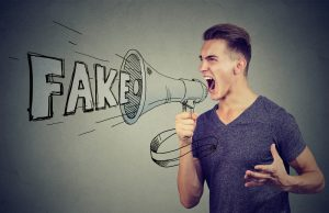 "Man yelling into microphone in front of text that reads ""fake"""