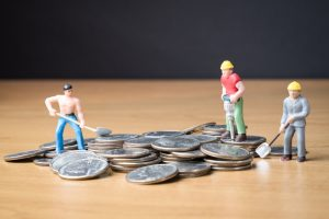 Toy figures of construction workers are placed on top of quarters. The image is meant to represent trickle-down economics for blue-collar workers.