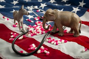 A photo of a stethoscope and prescription pills laid on top of the American flag. A toy figure of an elephant and a donkey face off, symbolizing the ongoing battle between Republicans and Democrats over Obamacare.