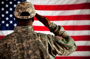 A photo of an African-American soldier saluting the U.S. flag.
