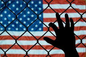 Someone reaching through a wire fence. On the other side is an American flag.