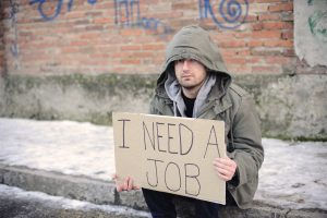 "A homeless man holding a sign that reads, ""I need a job."""