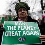 """A protestor holds a sign that reads, """"Make the planet great again."""""""