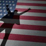 A shadow of a man projected onto the American flag.