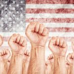 A bunch of fists raised in front of the American flag.