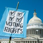 """A sign that reads """"voting rights"""" pictured alongside the U.S. Capitol."""