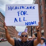 "A photo of a man holding a sign that reads, ""Health care for all now!"""