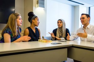 A diverse group of college student having a discussion.