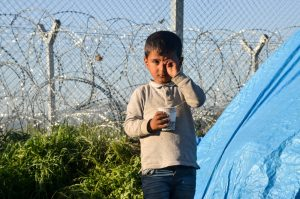 A Hispanic boy crying. There is a barbed wire fence behind him and a tent at his side.
