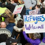 """Protestors hold signs that read, """"Refugees welcome."""""""