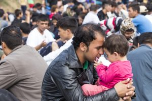 An immigrant father consoling his young daughter.