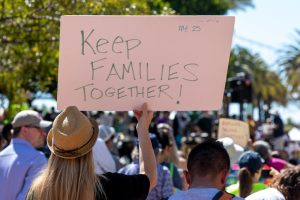 "A protestor holds a sign that reads, ""Keep families together."""