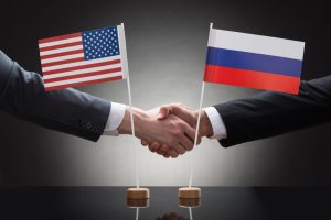 Two men shake hands in front of the American flag and the Russian flag.