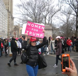 "A woman holding a sign that reads, ""Women for Trump."""