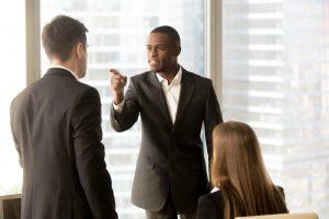 A black businessman scolds a white businessman.
