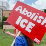 "A protestor holds a sign that reads ""abolish ICE."""