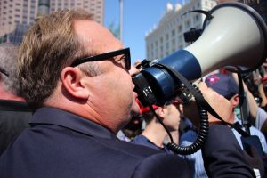 Alex Jones uses a megaphone to voice his opinion as he increases the level of tension between protesters.