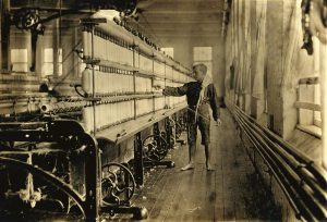 A young boy working in a factory. Photo taken in 1909.