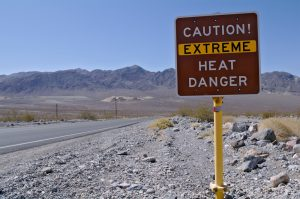 "A sign posted in the middle of a desert that reads, ""Caution: Extreme heat danger."""