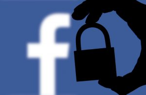 Someone holding a lock next to Facebook's logo.