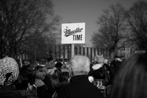 """A protestor holds a sign that reads, """"It's Mueller time."""""""