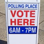 A sign directing voters to a polling place.