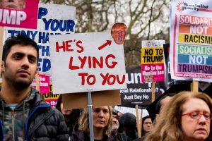 A Trump protestor holds a sign that claims that the president is lying to the people.