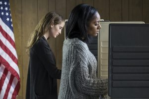 Two women standing in voting booths.