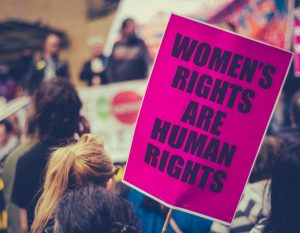 "A protestor holds a sign that reads, ""Women's rights are human rights."""