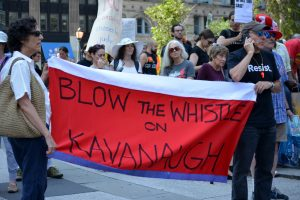 """Protestors hold a sign that reads, """"Blow the whistle on Kavanaugh."""""""