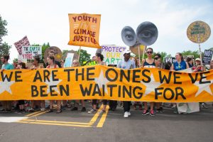 "Climate change activists holding a banner that reads, ""We are the change we have been waiting for."""