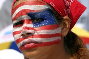 A Hispanic woman with the American flag painted on her face.