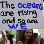 "A climate change activist holds a sign that reads, ""The oceans are rising and so are we."""