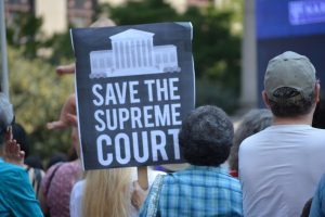 "A Kavanaugh protester holds a sign that reads, ""Save the Supreme Court."""