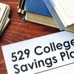 "A document titled ""529 College Savings Plans"" laid next to books and money."