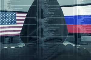 A computer hacker. In the background are the U.S. and Russian flags.