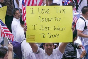 "A Mexican-American immigrants hold a sign that reads, ""I love this country. I just want to stay."""