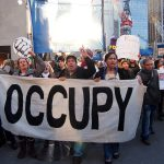 "Occupy Wall Street protesters march down the street carrying a banner that reads ""occupy."""