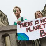 "Climate change activists hold a sign that reads, ""There is no planet B."""