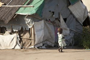 A malnourished child walks past the shack she and her family live in. Photo taken in South Sudan.