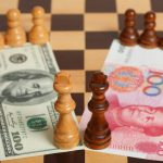 U.S. one hundred dollar bill and a Chinese one hundred yuan on a chess board.