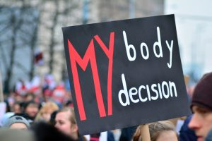 "A pro-choice rally. An activist holds a sign that reads, ""My body, my choice."""