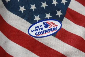 "A sticker that reads ""my vote counted."" It is pasted onto an American flag."
